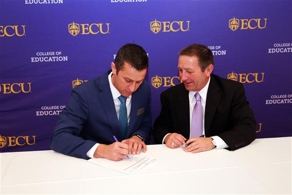 Michael White (left) signs the agreement