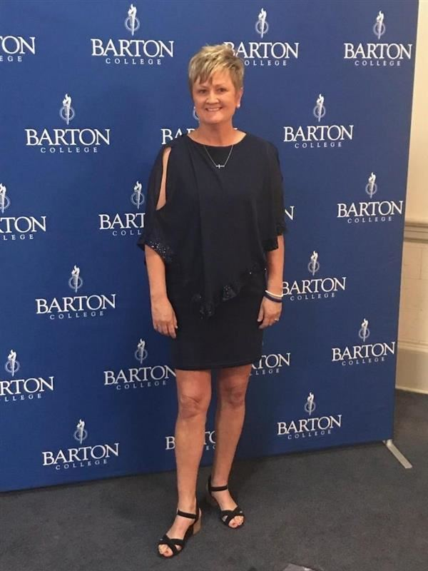 Coach Jackie Copeland in front of Barton College sports backdrop
