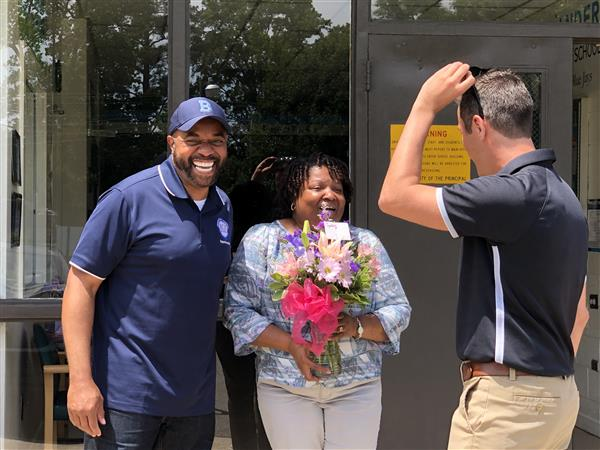 Dr. Smallwood and Mr. White and Clara Lee, Principal of the Year. with flowers