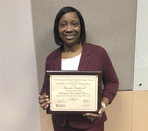Principal Tawanda Smallwood holding certificate of program completion