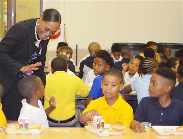 Dr. Edmonds saying hello to students in the cafeteria, eating lunch at Windsor Elementary